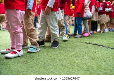 Queue of Asian kids in school uniform standing in line