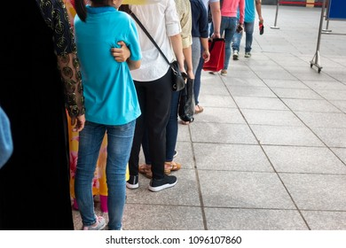 Queue of Asian people wait in line in urban street