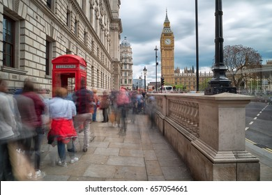 queue of people at one of the famous red telephone boxes in London