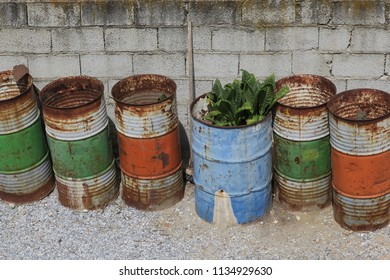 a queue of six multi colored oildrums