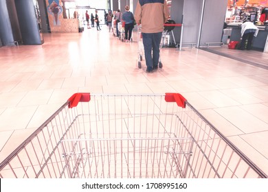 Queue at supermarket pov from empty shopping cart - Line of people respecting social distancing measures inside department store - Concept of everyday life in the time of covid-19 pandemic - Image