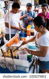 Quezon City / Philippines - February 15, 2019: a young Filipino lady selling fish ball, kikiam, squid balls and crispy quail egg