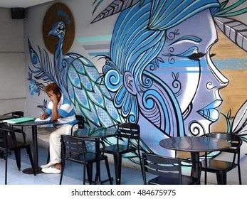 QUEZON CITY, PHILIPPINES - SEPTEMBER 13, 2016: A man sits in front of an artwork on the wall of a restaurant at The Sky Garden at the SM City North Edsa.