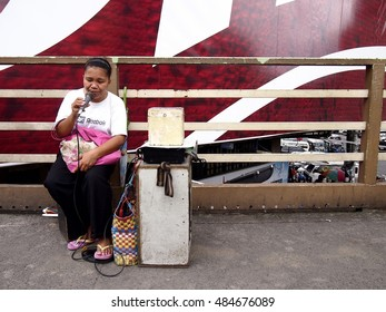 QUEZON CITY, PHILIPPINES - SEPTEMBER 13, 2016: A blind singer performs at a foot bridge to earn money.