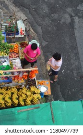 QUEZON CITY, PHILIPPINES-SEPTEMBER 15, 2018: A woman buying fruits from a man in Frisco Market. The country has experienced high inflation rates recently causing increased prices of goods.