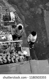 QUEZON CITY, PHILIPPINES-SEPTEMBER 15, 2018: A woman buying tropical fruits from a man selling it in Frisco Market. Photo in black and white.