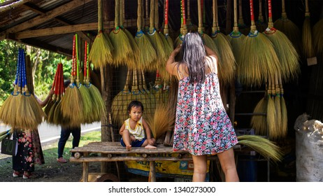 Quezon, Philippines - March 13, 2019: A mother taking care of her broom business while taking care of her child in Real, Quezon, Philippines