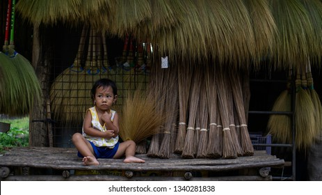 Quezon, Philippines - March 13, 2019: Young daughter left sitting on a broom business store while mother is talking to customers in Real, Quezon, Philippines.