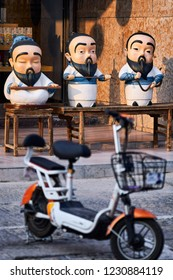 Qufu / China - October 13th 2018: Street scene, cartoon-like statues of Confucius.  Qufu is famous as the birthplace of philosopher Confucius.