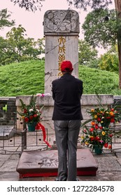 Qufu, Shandong / China - October 13th 2018: Man paying respect at the Tomb of Confucius, part of the UNESCO World Heritage Site Temple and Cemetery of Confucius in Qufu, birthplace of Confucius.