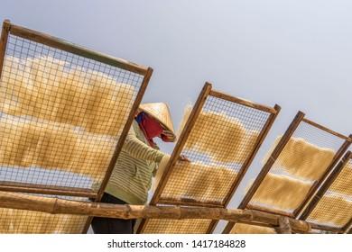 Qui nhon, Vietnam- Mar 13, 2017: A woman is drying her vermicelli under the sun at Qui nhon, Vietnam.