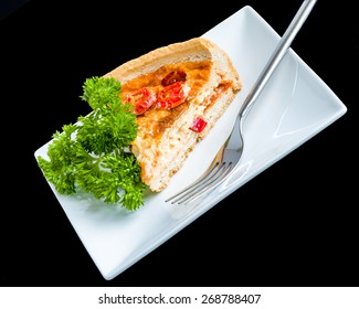 Quiche Diagonal. A slice of quiche garnished with green herbs on a square white plate.