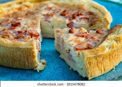 Quiche Lorraine tart on a turquoise plate with a slice cut out.