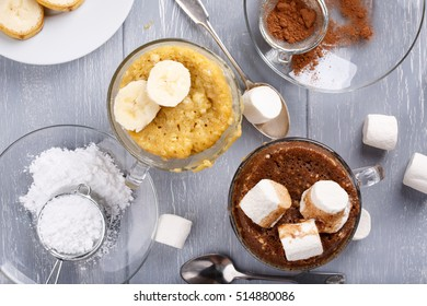 Quick banana cake and chocolate cake with marshmallow in a glass mugs from microwave. Top view.