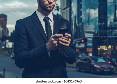 Quick business message. Night time image of confident young businessman in formalwear holding smart phone and looking at it while standing outdoors with cityscape in the background