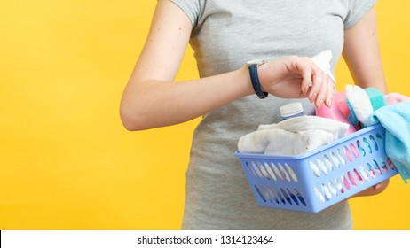Quick cleaning. Organized wife time management. Woman torso with basket of supplies looking at watch. Copy space on yellow background.