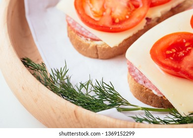 Quick cooking sandwiches with ham meat cheese tomato dill on wooden plate