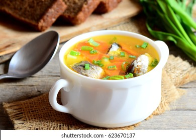 Quick, easy and delicious fish soup. Homemade fish soup with potatoes, carrots and green onions in a bowl. Rye bread pieces, fresh green onion, spoon on vintage wooden table. Closeup