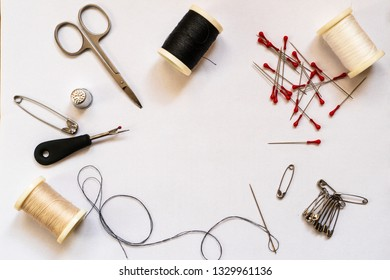 Quick fix sewing kit accessories and tailor equipment for sewing and repairing. Accessories and tools for needlework: scissors, thread spools, needles, pins and safety pins, thimble, flat lay.