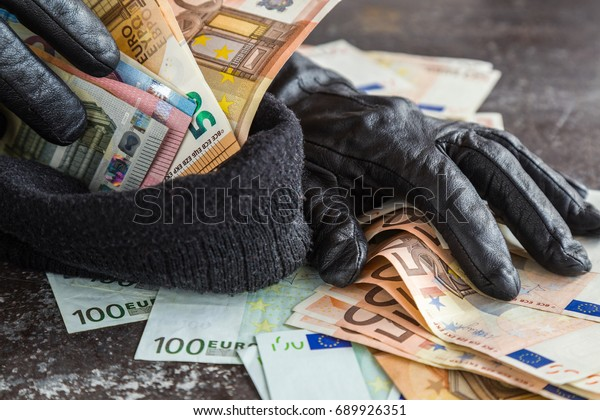 Quick loot in the store. Thief' s hands in black leather gloves stealing a money and putting it in the his hat. Many money.