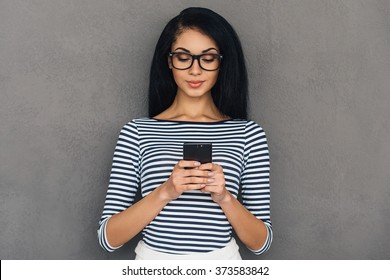 Quick message to friend. Attractive young African woman holding smart phone and looking at it while standing against grey background