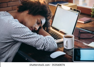 Quick nap. Side view of young African man sleeping on laptop with eyes closed while sitting at his working place