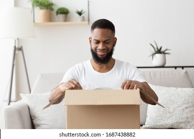 Quick purchases in online store. Glad african american millennial guy opens big box