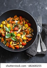 Quick ratatouille in a cast iron skillet on a dark background, top view. Steamed vegetables - vegetarian food concept