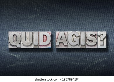 quid agis (what's up) question made from metallic letterpress on dark jeans background