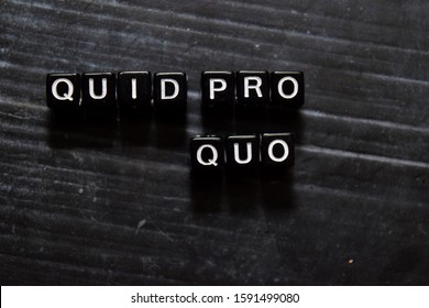 Quid Pro Quo in Latin on wooden cubes. On table background