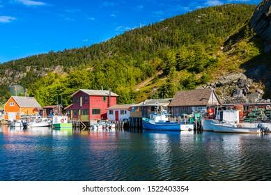 Quidi Vidi, Newfoundland / Canada - September 15, 2019: fishing boats docked on a sunny day in Quidi Vidi near St John's Newfoundland.  Calm water reflects the vibrant colours of the fishing shacks.