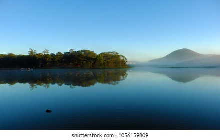 Quiet, calm and peaceful scenery of Than Tho  lake, Da Lat city, Viet Nam in early morning, pine tree in forest reflect on water make romantic and fresh view for ecotourism in summer