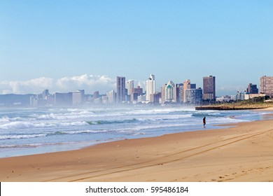 Quiet early morning beach against blue cloudy sky and city skyline in Durban, South Africa