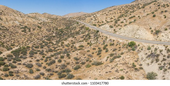 Quiet empty road borders the vast wilderness of the Mojave desert in the southwest of United States.