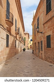 A quiet empty sunlit picturesque cobbled narrow street in ciutadella menorca with balconies and street lamps on colorful old houses