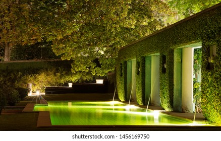 Quiet fountain and swimming pool in a modern architecture house. The long exposure enhances the light and the green color of the foliage