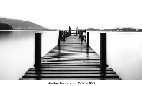 Quiet landscaped gardens with room for text, pier in the calm water sea.