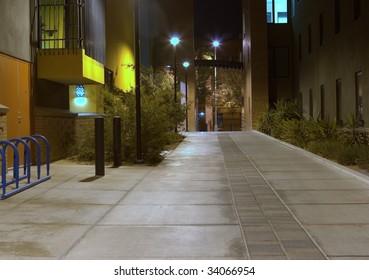 A quiet looking sidewalk between two buildings taken at night time