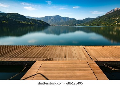 Quiet and peaceful view over a lake with mountains in the distance, standing on a dock on a summer day