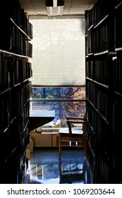 Quiet, secluded workplace at university library, dark before stark bright light through a window.