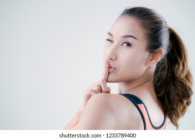 Quiet sign,Beautiful woman silent quiet gesture with finger and closed one eye,Secret girl saying hush be quiet with finger on lips gesture isolated,Nice and playful of quiet sign,Body language,
