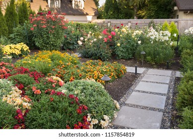 A quiet stone path winds trhough a colorful backyard garden.