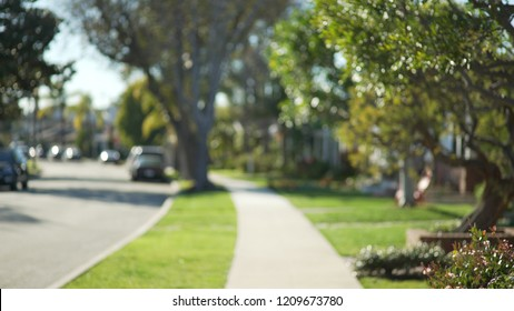 Quiet street scene of the sidewalk and idyllic homes in a suburban neighborhood