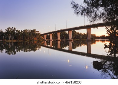 quiet sunrise on still Murray river under the bridge connecting Victoria and New South Wales states of Australia.