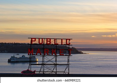 Quiet sunset over Puget Sound in Seattle, USA. Red fluorescent sign of Seattle famous Public Market and horizon over the land.