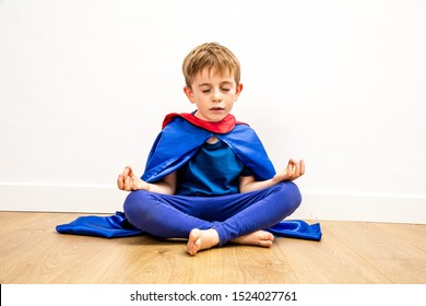 quiet superhero child breathing with zen yoga, mindfulness and relaxation, bare feet sitting for wellness, peace and strength, studio shot