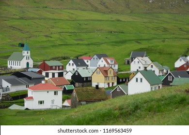 Quiet town in the vibrant green countryside under the steep grassy mountains in Faroe Islands. Picturesque view of a serene village in idyllic rural setting. Lush meadows around lovely small town.