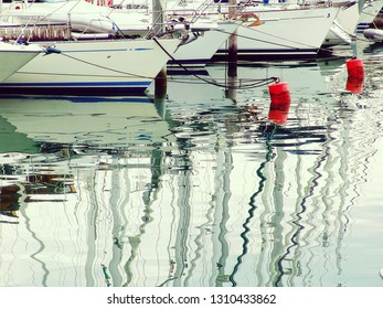 Quiet weather in harbor, water like a  mirror, boat reflections and ripples