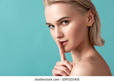 Quietness concept. Portrait of groomed blonde girl looking at camera and holding her index finger on lips. Copy space in left side. Isolated on blue background