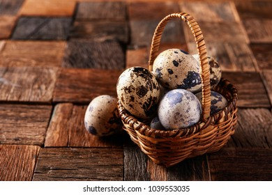 quil eggs in basket on wooden background